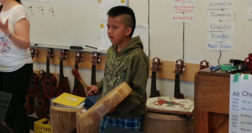 Student enjoys drumming in music class.